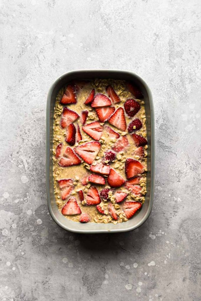 Baked oatmeal in a dish with the strawberries layered in.