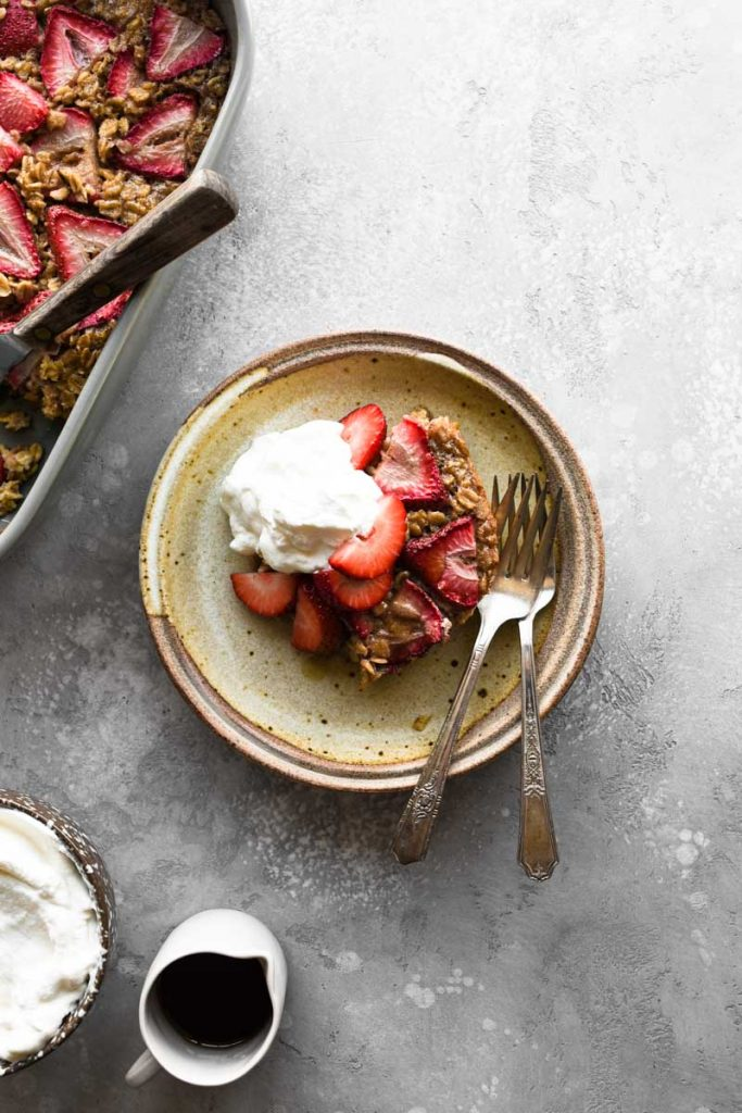 A plate of baked oatmeal with fresh strawberries on top