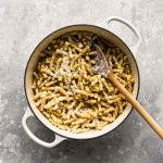 Finished pasta in pot with wood spoon