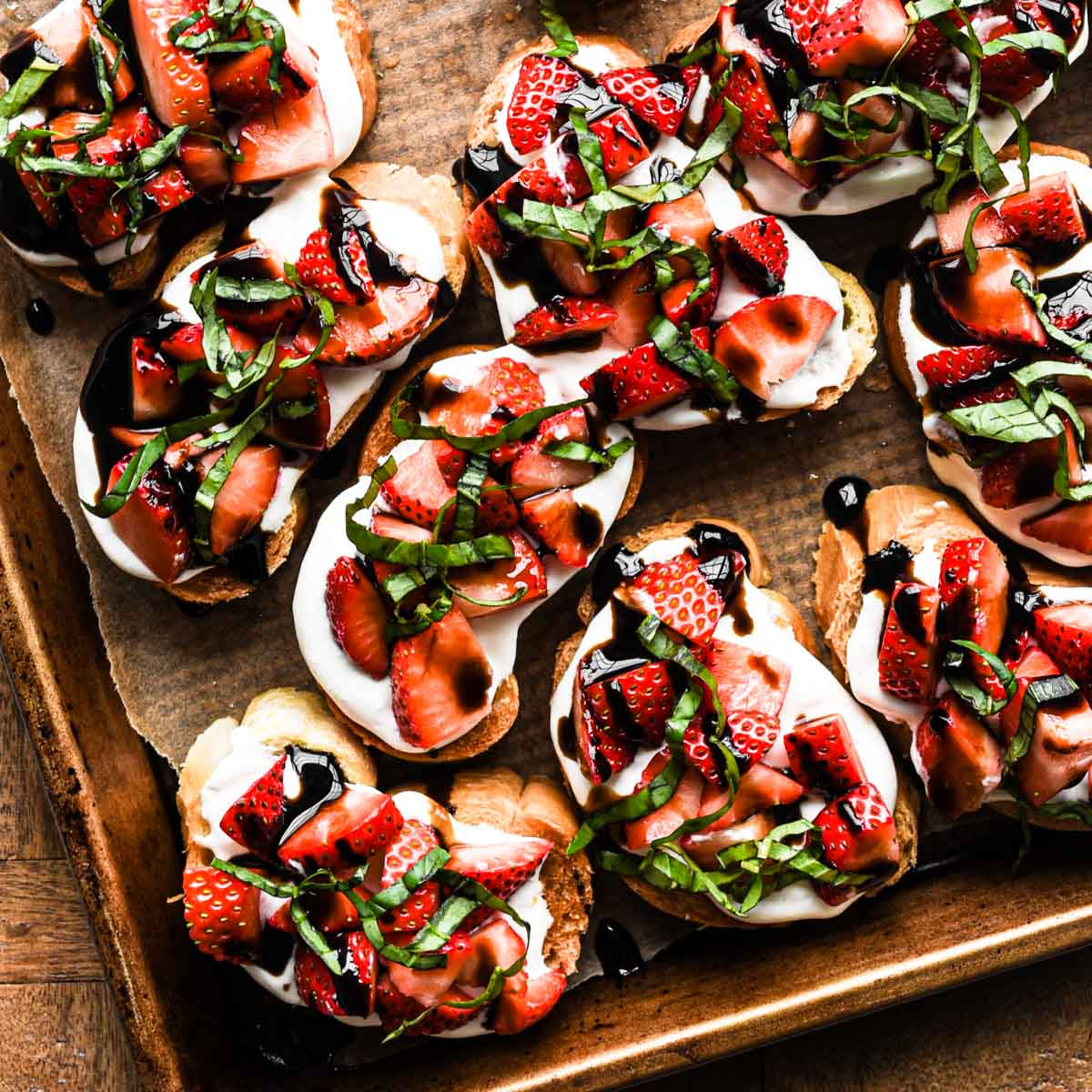 Strawberry Balsamic Crostini on a sheet tray with basil on top