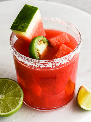 Up close image of a finished spicy watermelon margarita with watermelon slices and a salt rim.