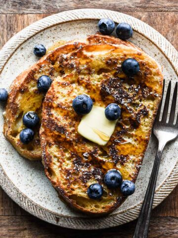 Up close of french toast with berries, syrup, and butter.