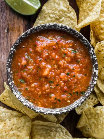 Up close of mango habanero salsa in a speckled bowl with chips.
